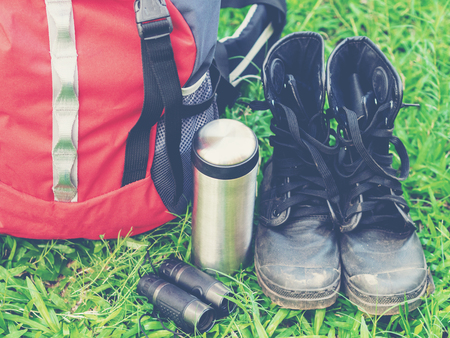 Hiking travel gear on glasses. Items include hiking boots, cup, map, binoculars. Flat lay of outdoor travel equipment items for mountain camping trip.