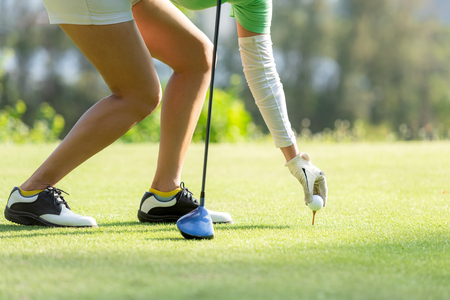Hand asian sporty woman putting golf ball on tee with club in golf course on evening on time for healthy sport. Lifestyle and Sport Concept 写真素材 - 125722718