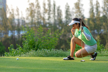 Sporty asian woman golf player crouching and study the green before putting shot in vacation and holiday. Sport and Healthy Concept Reklamní fotografie