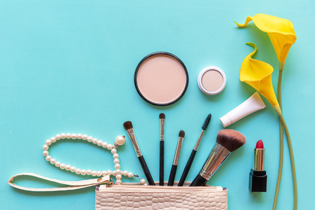 Makeup cosmetics tools and beauty cosmetics gift, products and facial cosmetics package lipstick with yellow flower on geen pastel background, top view and copy space.  Lifestyle Beauty Concept