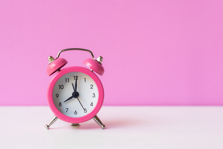 Alarm pink vintage alarm clock falling on the floor with color background.  Morning and Start up Concept