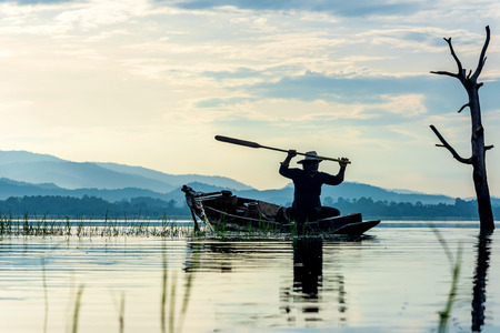 Fisherman action  on lake in the sunshine morning and silhouette fisherman outdoor on the boat, agriculture Thailand Banco de Imagens