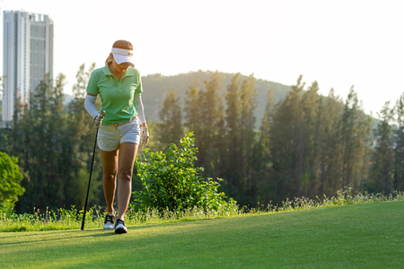Sport Healthy. Golfer asian sporty woman walking relax on fairway for the put golf ball on the green golf evening time in vacations day.  Healthy and Lifestyle Concept