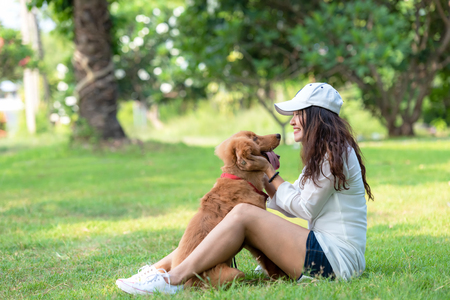 Asian smilling lifestyle woman playing and happy with golden retriever friendship dog in sunrise outdoor the summer park.