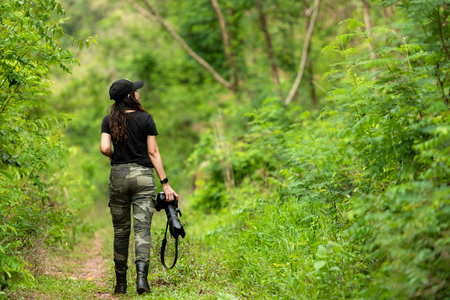 Professional woman photographer taking outdoor portraits with prime lens in the green forest nature. Travel  and Vacations Concept Banco de Imagens