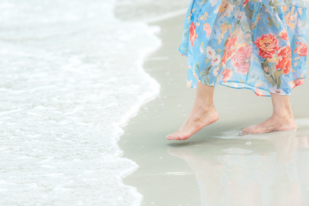 Close up leg lifestyle woman in long dress feeling relax and  happy on the tropical sand beach in summer day. Healthy Life.  Summer Concept.