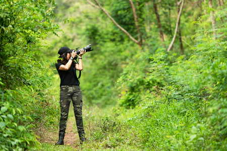 Professional woman photographer taking outdoor with prime lens in the green jungle rain forest nature. Travel  and Vacations Concept