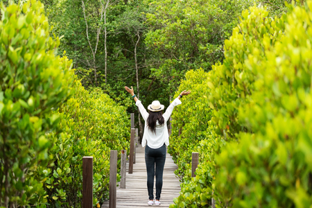 Traveler woman happy feeling freedom good and relax on the bridge wood in travel study nature forest and education natural. Travel and Vocation Concept Banco de Imagens