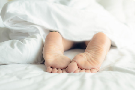 Lifestyle woman feet on the bed under white blanket in the morning. Sleeping and relax Concept Banco de Imagens