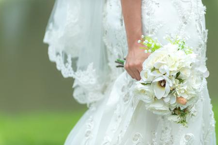 Bride holds a wedding bouquet. Bride wedding white dress in the garden. Nature Background Banco de Imagens