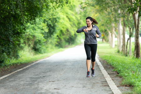 Running woman. Sport Women jogging during and check timing.  Outdoor Workout in a Park. Weight Loss and Healthy Concept