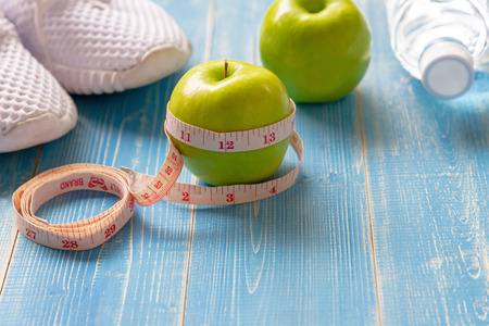 Diet and Healthy life loss weight Concept. Green apple and Weight scale measure tap with fresh vegetable and sport equipment for women diet slimming. Top view and copy space Banco de Imagens