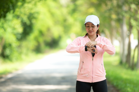 Running woman. Sport Women set up watch running before jogging.  Outdoor Workout in a Park. Weight Loss and Healthy Concept