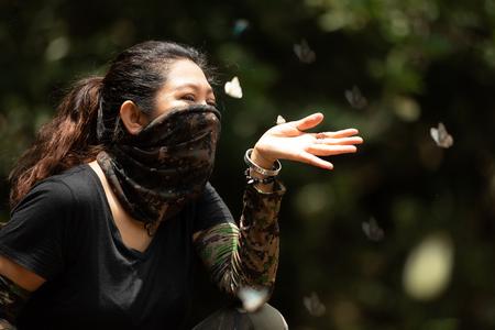 Hiker woman playing with a butterfly in the green jungle forest nature. Banco de Imagens