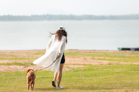 Asian lifestyle woman playing and running  with golden retriever friendship dog in sunrise outdoor the summer river park.