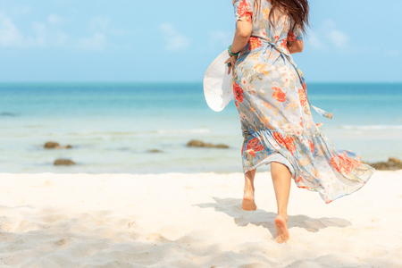 Lifestyle woman wearing fashion  dress summer running on the sandy ocean beach. Happy woman enjoy and relax vacation. Lifestyle and Travel Concept Banco de Imagens