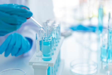 Scientifiques analysant les données de l'étude et évaluant le microscope. Des chercheurs en soins de santé effectuant des recherches avec des tests chimiques au compte-gouttes et travaillant dans un laboratoire de sciences de la vie.