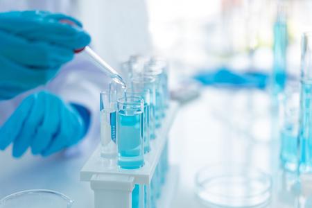 Wissenschaftler analysieren Studiendaten und bewerten das Mikroskop. Forscher im Gesundheitswesen, die einige Forschungen mit Tropferchemikalientests durchführen und im Life-Science-Labor arbeiten.