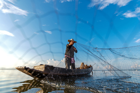 Fisherman action when fishing net  on lake in the sunshine morning outdoors on the boat. Agriculture Industry, Thailand