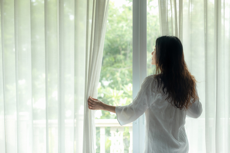 Lifestyle Women open window after get up the white bed in morning sunrise relax mood . Lifestyle Concept.