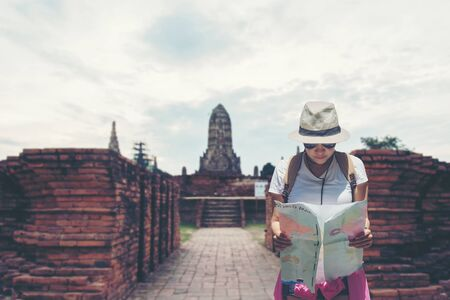 Traveler and tourist asian women check map with backpack walking in temple Ayuttaya ,Thailand.  Travel Concept