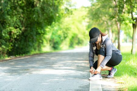Running woman tying laces of running shoes before jogging through the road in the workout nature park.  Weight Loss and Healthy Concept