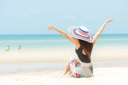 Summer Holiday. Lifestyle woman chill big white hat and wearing bikini fashion summer trips sitting on the sandy ocean beach. Happy woman enjoy and relax vacation. Lifestyle and Travel Concept Banco de Imagens