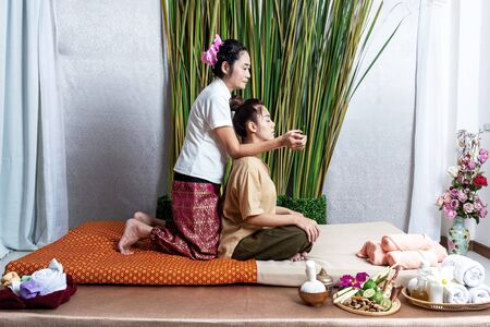Thai Masseuse doing massage for lifestyle woman in spa salon. Asian beautiful woman getting Thai herbal massage compress massage in spa.She is very relaxed. Healthy Concept. Banco de Imagens