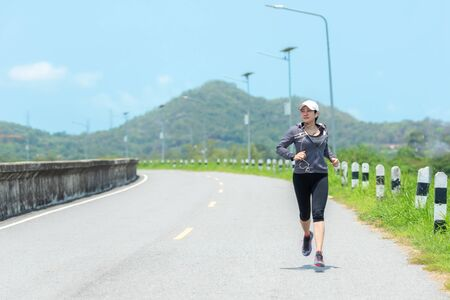 Sporty Woman runner running through the road. Workout in a Park. Outdoor Workout in a Park. Weight Loss and Healthy Concept