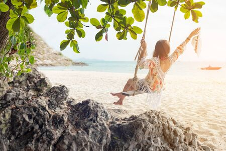 Summer Vacations.  Lifestyle women relaxing and enjoying swing on the sand beach, fashion stunning women on the tropical island so happy and luxury in holiday summer.  Travel and Summer Concept
