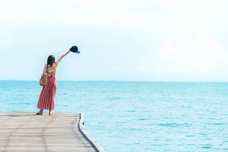 Summer Vacation. Smelling asian women relaxing and freedom on the bridge, so happy and luxury in holiday summer, outdoors blue sky background. Travel and lifestyle Concept.