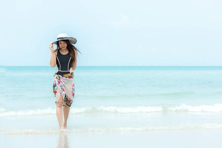 Summer Holiday. Lifestyle woman chill holding big white hat and wearing bikini fashion summer trips walking on the sandy ocean beach. Happy woman enjoy and relax vacation. Lifestyle and Travel Concept