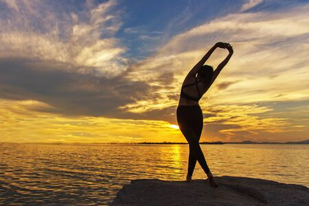 Silhouette healthy woman lifestyle exercising vital meditate and practicing yoga on the rock in beach at sunset. Healthy Concept.