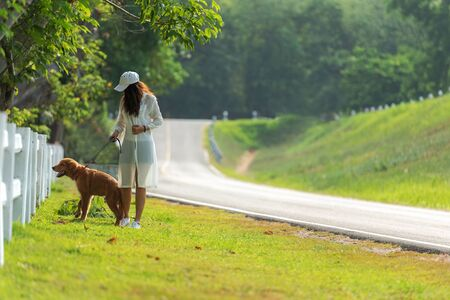 Asian lifestyle woman walking so happy with golden retriever friendship dog near the road in sunrise outdoor the summer park.