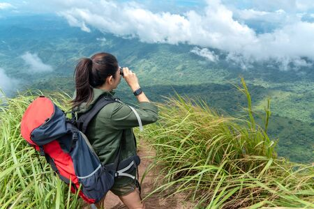 Hiker asia woman look binoculars and standing on mountain. Female adventure backpack and camping on hike in outdoor nature. Travel Concept Banco de Imagens
