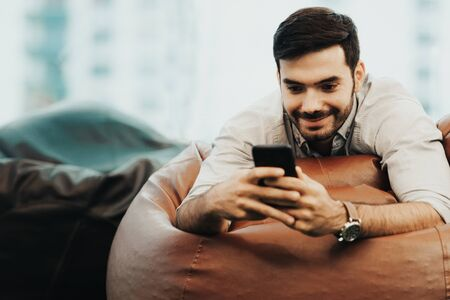 Smiling businessman using and relax smartphone device while sitting on sofa at home.  Man cheerful hipster guy typing an sms message at social network.  Technology Concept