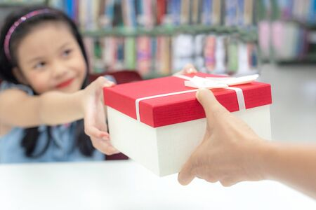 Gift box for kids girl. White box with red bow in the smiling asian girl hands for give a gift in the library.  Anniversary and Celebration Concept Banco de Imagens