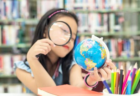 Student asian smiling child studying and education Earth Globe in library, select focus.   Education Concept Banco de Imagens