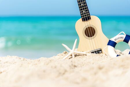 The Summer day with Guitar ukulele items travel for relax and chills on the beautiful beach and blue sky background,copy space. Travel and Summer Concept Banco de Imagens