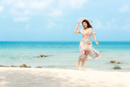 Summer Holiday. Lifestyle smiling asian woman wearing dress fashion summer trips relax on the sandy ocean beach. Happy woman enjoy and relax vacation. Lifestyle and Travel Concept