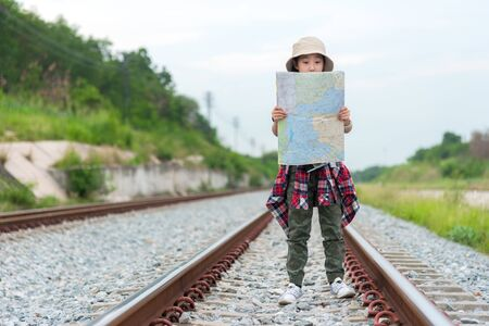 Student asian girl and traveler with backpack adventure holding map to find directions near train station outdoor for study and education nature. Travel and Lifestyle Concept