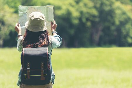 Student asian women and traveler with backpack adventure holding map to find directions in the jungle forest outdoor for study and education nature. Travel and Lifestyle Concept