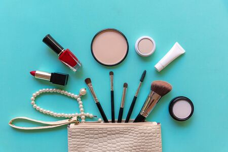 Makeup cosmetics tools background and beauty cosmetics, products and facial cosmetics package lipstick, eyeshadow on the blue background, top view and copy space.  Lifestyle Beauty Concept