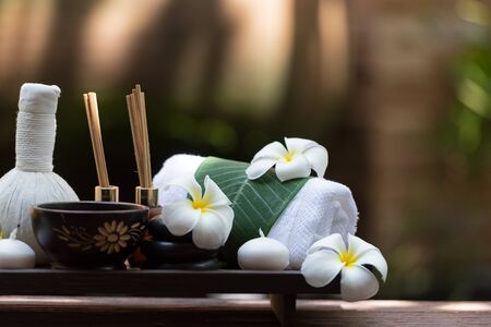 Thai spa composition treatments aroma therapy with candles and Plumeria flowers on wooden table close up. Healthy and Relax Concept Banco de Imagens