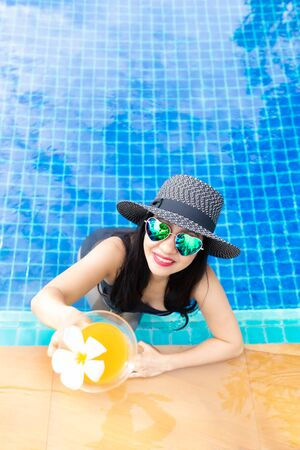 Summer time and Vacations. Women lifestyle relaxing and drinking juice orange so happy in luxury swimming pool sunbath, summer day at the beach resort in the hotel. Summer Concept