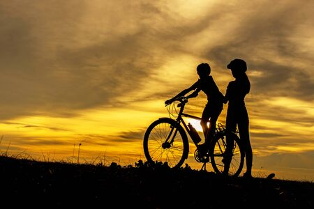 Silhouette biker lovely family at sunset over the ocean.  Mom and daughter bicycling chill and relax at the beach.  Lifestyle Concept.