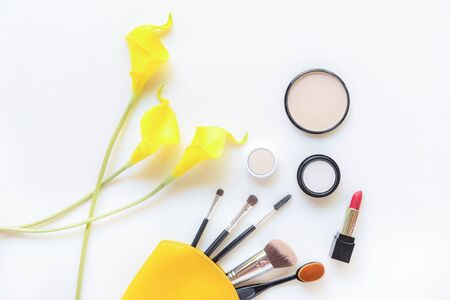 Makeup cosmetics tools and beauty cosmetics gift, products and facial cosmetics package lipstick with yellow lily flower on the white background, top view and copy space. Lifestyle Beauty Concept Banco de Imagens