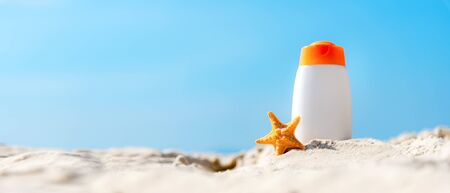 Protective sunscreen or sunblock and sunbath lotion for healthy care skin woman in white plastic bottles with starfish on tropical beach, summer accessories in holiday, copy space for text banner.  Summer Concept