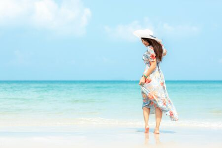 Summer Holiday.  Lifestyle smiling asian woman wearing dress fashion summer trips relax on the sandy ocean beach. Happy woman enjoy and relax vacation. Lifestyle and Travel Concept Banco de Imagens