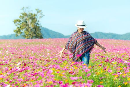 Traveler Asian women walking in the flower field and hand touch cosmos flower, freedom and relax in the flower meadow, blue sky background. Lifestyle Concept